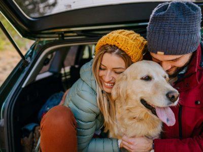 A couple hug the dog in car